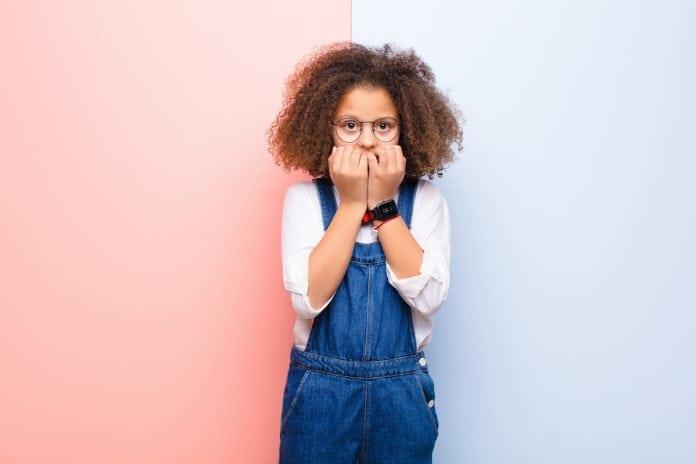 Ansiedade na volta às aulas: 9 ações para ajudar as crianças; menina de macacão jeans e cabelo crespo está com as duas mãos sobre a boca