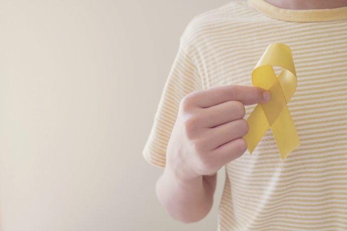 Câncer em crianças: saiba os sintomas aos quais ficar atento; mão de criança segura fitinha amarela que simboliza o mês de fevereiro e a luta contra o câncer infantojuvneil