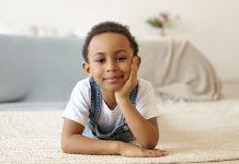 Autonomia emocional dos filhos: é preciso ficar atento a isso; criança deitada no chão com rosto apoiado sobre mão olha para câmera com um sorriso no canto da boca