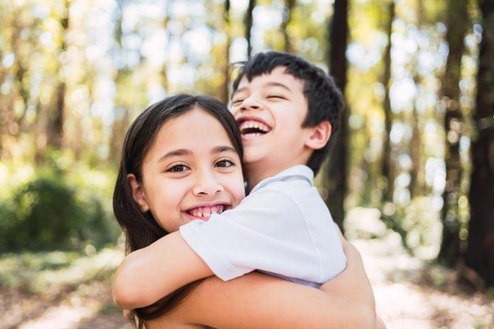 Cada filho é único: saiba como agir para despertar o amor entre os irmãos; garota abraça irmão mais novo sorridente em espaço aberto com árvores ao fundo