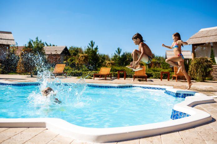 Férias em família: como se divertir sem prejudicar o orçamento; duas crianças pulam na piscina de resort