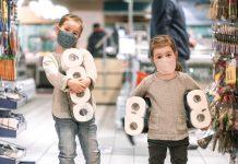 Você costuma levar o seu filho ao supermercado?; duas meninas de máscara e casacos seguram rolos de papel higiênico com os braços