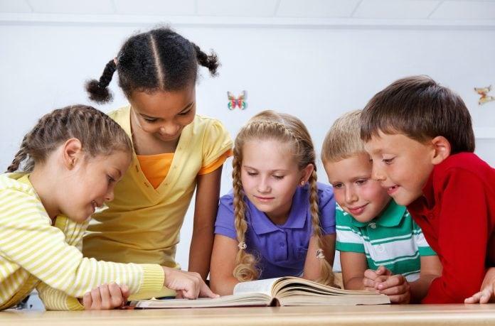 Como lidar com a transição da Educação Infantil para o Fundamental; 5 alunos de etnias diversas olham para livro sobre a mesa
