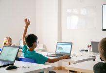 A tecnologia deve servir à vida e resgatar a alma das crianças na escola; aluno sentado à frente de mesa com computador levanta o braço em sala de aula