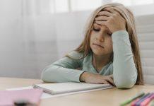 Estresse tóxico e estresse positivo: como eles afetam os pequenos; menina está sentada com mão na testa e outro sobre caderno sob a mesa