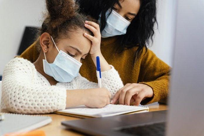 Ensino remoto para crianças com TDAH: como fazer isso dar certo; Menina de máscara, com aproximadamente 8 anos segurando uma caneta. Ao lado, mulher também de máscara ajudando a criança.
