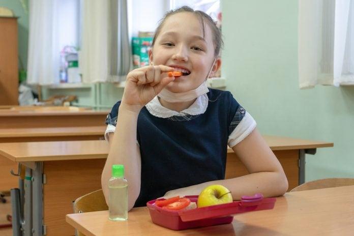 Lanches saudáveis para levar na escola; Menina asiática comendo um pedaço de cenoura. A frente dela, uma lancheira com frutas e um vidro de alcool em gel sobre a mesa.