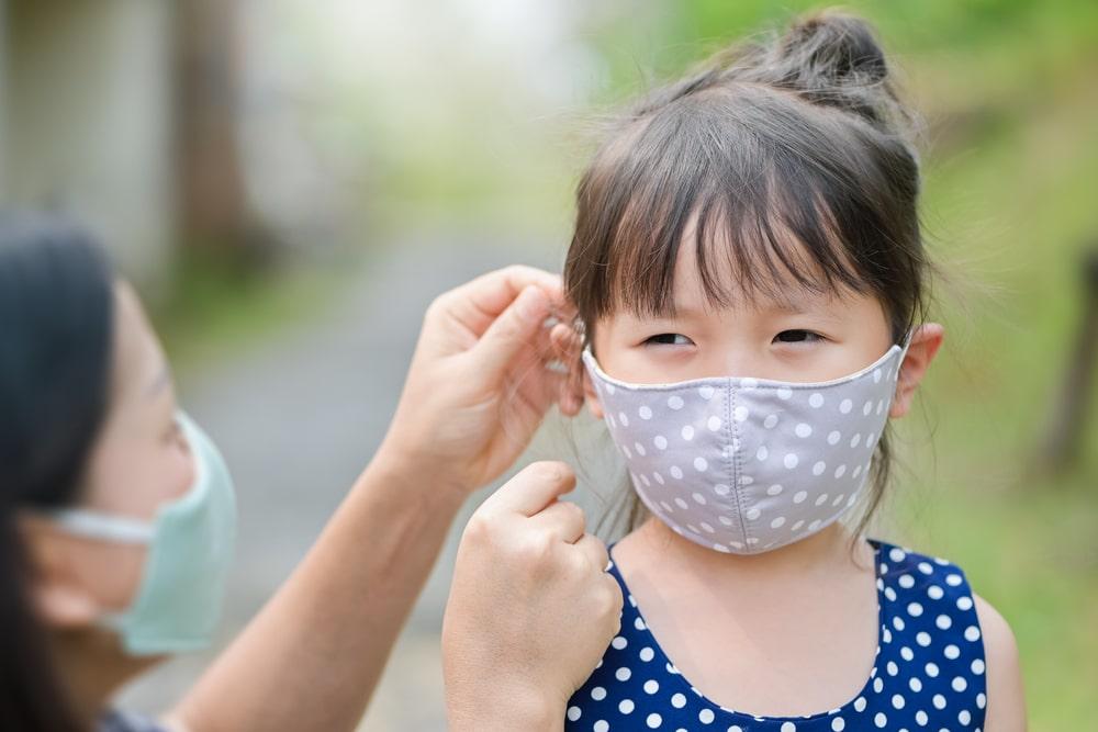 Máscara para crianças: qual é a mais segura agora?; mulher adulta mexe na máscara de tecido de cor cinza com bolinhas que menina oriental está usando