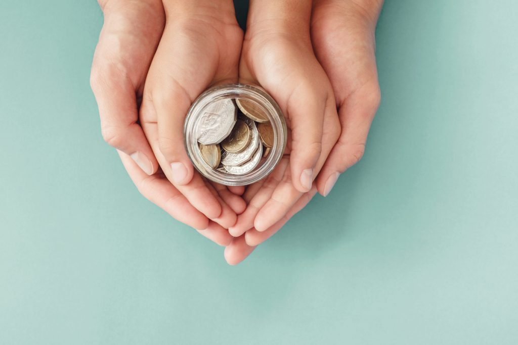 7 erros a evitar na hora de dar mesada aos filhos; mãos de um adulto envolvem mãos de uma criança que segura várias moedas