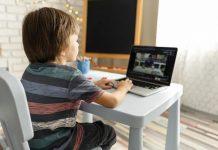 O primeiro dia de aula online; menino está sentado em escrivaninha olhando para professor em tela de computador