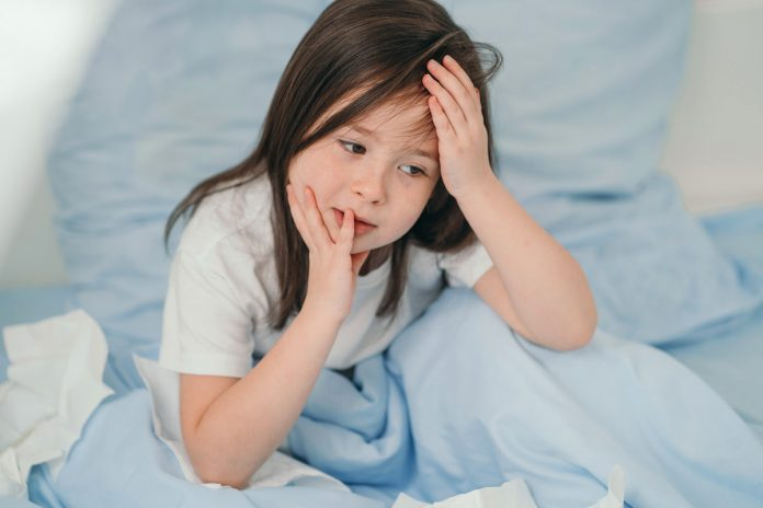 Dengue ou Covid-19: como diferenciar os sintomas em crianças; menina deitada na cama com com uma mão na cabeça e outra no rosto