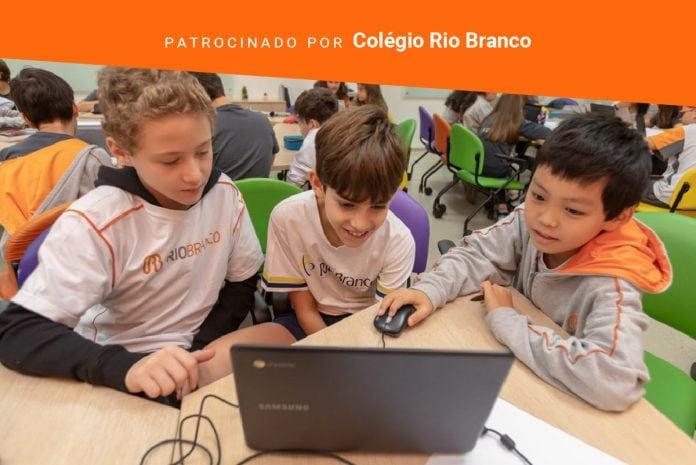 Afinal, o que é a alfabetização?; imagem mostra três crianças olhando para um computador