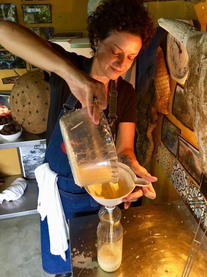 Levar as crianças para a cozinha pode ajudar no desenvolvimento delas; Mulher branca em uma cozinha coando um líquido em uma peneira.