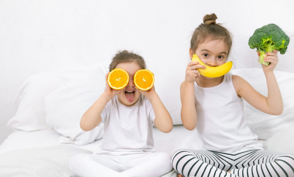 10 alimentos para garantir uma boa noite de sono para os pequenos! Duas meninas sentadas em uma cama branca. A menor segura duas metades de laranja na altura dos olhos. A maior segura uma banana na altura da boca, simulando um sorriso e um brócolis na outra.
