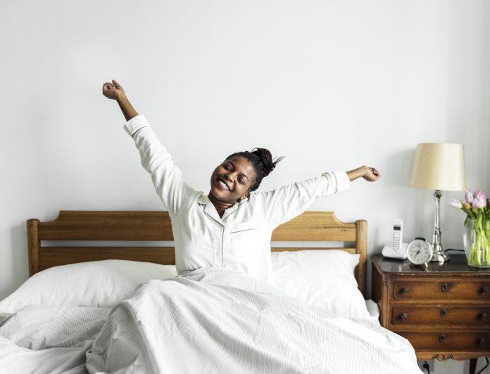 Xô, preguiça! Um exercício mental para levantar da cama com ânimo; mulher negra de camisa branca se espreguiça na cama sorridente com os braços abertos