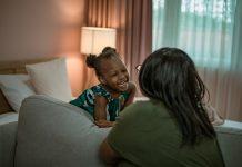Qual a diferença entre amar e mimar os filhos?; mãe negra de costas olha para filha negra que ri e está com cotovelos apoiados sobre sofá