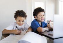 Aulas remotas: como transformamos os desafios em aprendizados; dois irmãos estudam - um no desktop e outro escreve no papel