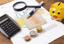 Quer fazer um investimento para seu filho? Invista no seu futuro!; moedas, lupa, caneta, papeis e calculadora sobre mesa