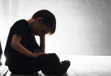 Atitudes que ajudam a identificar a ansiedade nas crianças; menino está sentado, de cabeça baixa apoiada sobre mão