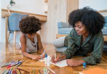 7 princípios que pais e escolas devem ensinar às crianças; deitados no chão, mãe e filho negros fazem desenho sobre papel