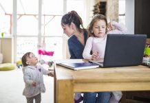 Parentalidade, como o próprio nome diz, não é acerca da criança, mas dos pais e os desafios que enfrentam ao criar os filhos; mãe com criança no colo e computador à frente na mesa olha para outra criança em pé ao lado da cadeira