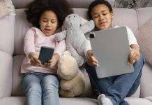 Seu filho não sai do celular? Existe uma explicação (no cérebro) para isso; uma menina de cabelos volumosos pretos segura o celular com as mãos e olha para a tela enquanto um menino segura um tablet e igualmente olha para a tela