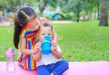 Leite de vaca, fórmulas e compostos lácteos: saiba quando são indicados; bebê asiático sentado sobre grama no parque segura copo de transição com ajuda da irmã mais velha