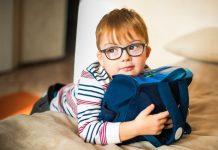 2020: o ano que mais prejudicou a visão das crianças; menino de óculos apoia tronco sobre cama e segura bolsa com os dois braços