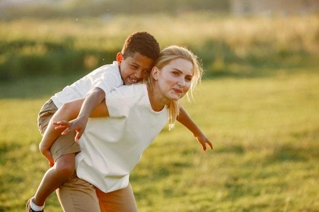Criar uma criança é fácil, mas educar...; mulher loira carrega criança morena nas costas em área verde ao ar livre