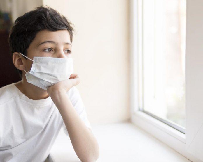 SBP avalia que mortes e hospitalizações por coronavírus em crianças estão em queda; menino com máscara e mão no queixo olha pela janela