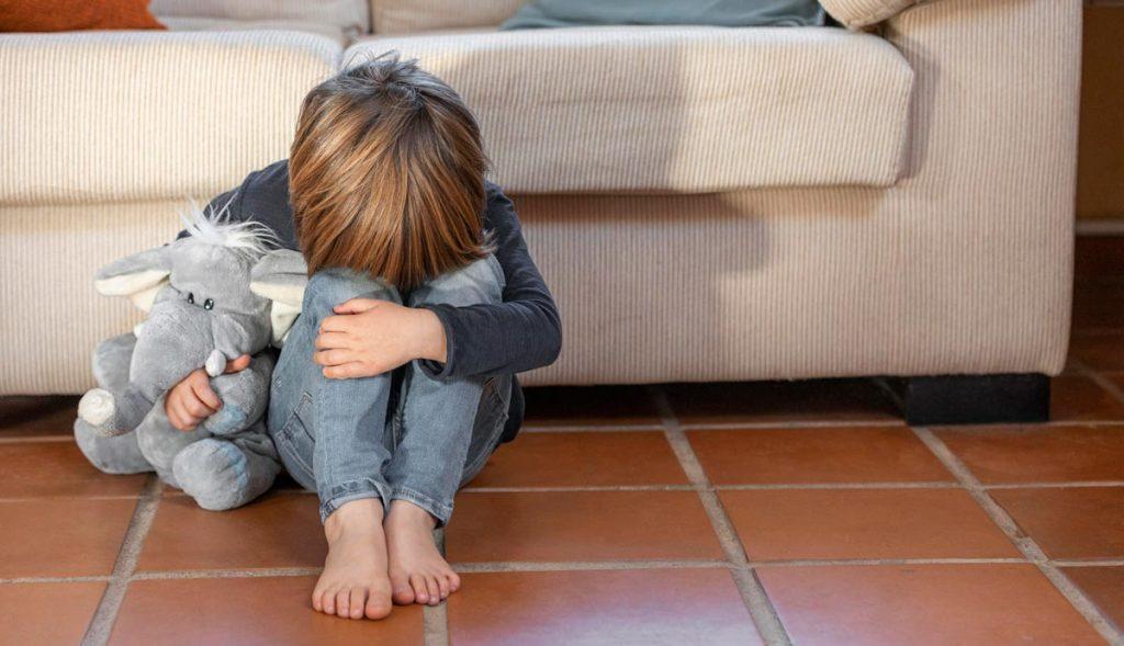 Validar as emoções é acolher a criança quando ela chora _ e não repreendê-la; menino está no chão com cabeça baixa apoiada sobre pernas com joelhos dobrados