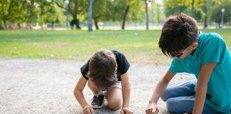 SBP alerta para contaminação de crianças por chumbo; dois meninos desenham com giz no chão em espaço verde ao ar livre