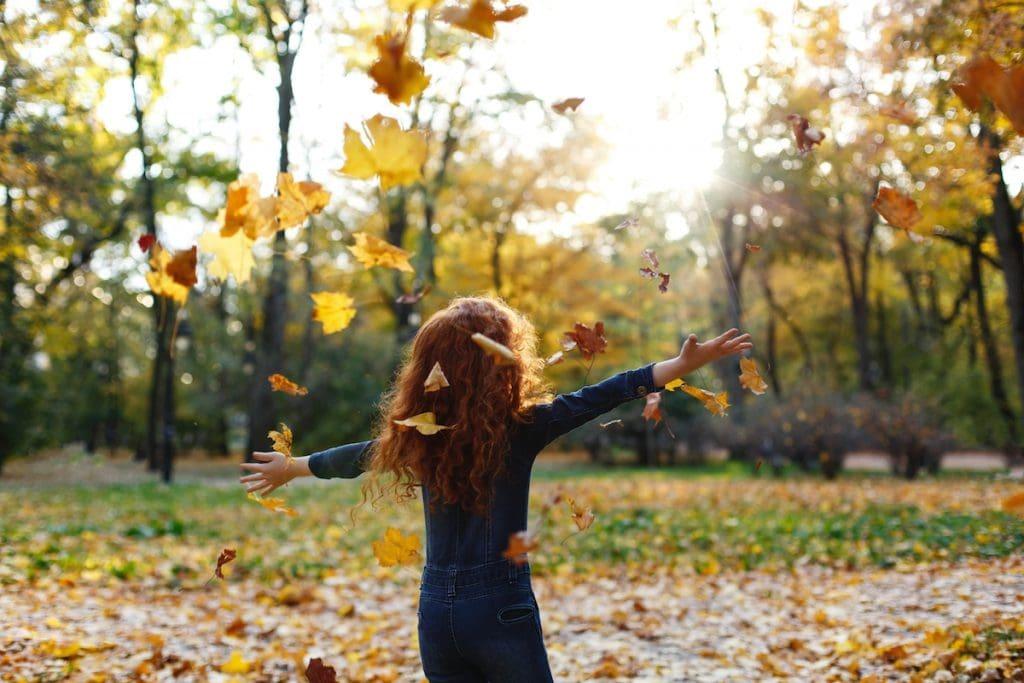 Crianças perto da natureza têm menor risco de desenvolver TDAH; menina está de braços abertos em jardim ao ar livre cheio de folhas secas