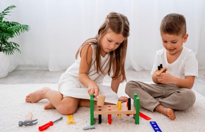 Como saber a hora de deixar a criança sozinha em casa?; menina e menino brincam no chão com peças de encaixe e ferramentas de brinquedo