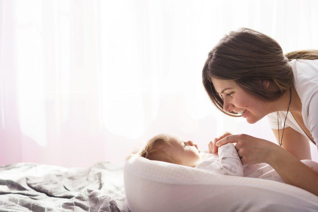 Pandemia pode atrapalhar desenvolvimento da linguagem em crianças; mãe olha para bebê deitado na cama