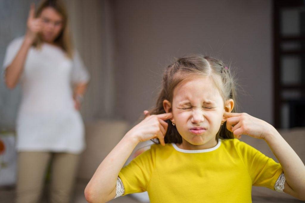 'Eu te odeio, mãe.' Frases como essa são comuns na sua casa?; menina de olhos fechados e blusa amarela tampa ouvidos com os dedos, no fundo, mulher adulta olha para ela