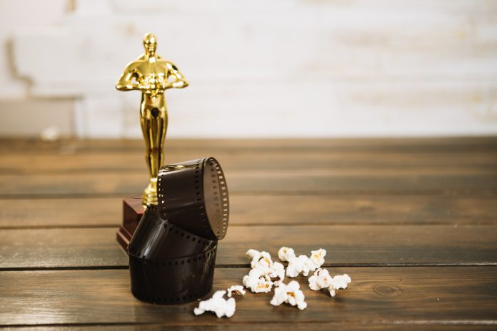 Estátua do Oscar com rolo de filme e pipoca