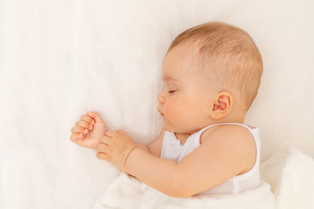 Como fazer o bebê dormir sozinho: conheça as principais técnicas de sono; bebê dorme na cama com o corpo de lado