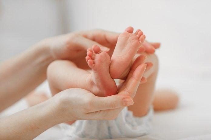 Câmara aprova texto que amplia doenças rastreadas no teste do pezinho; mãos de adulto seguram pés de recém-nascido