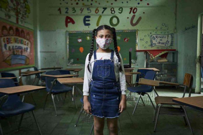 Pandemia pode afetar uma geração inteira de crianças, alerta Unicef; menina em pé dentro de sala de aula com máscara