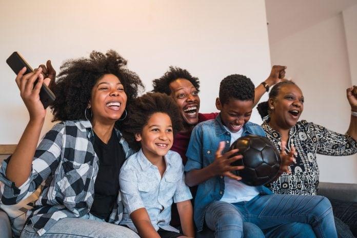 101 coisas para fazer com as crianças antes que eles cresçam; família afro sentada junta no sofá vibra por algo que vê na TV