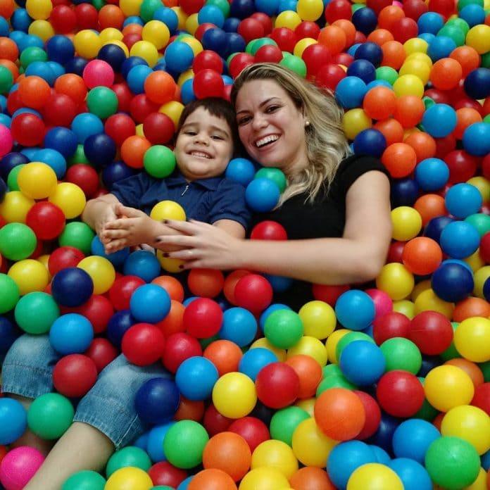 Superdotado: conheça as características da criança com altas habilidades + mãe e filho deitados dentro de uma piscina de bolinhas coloridas.