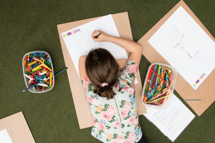 'Pinafamília', programa da Pinacoteca de São Paulo, agora tem formato digital; menina deitada no chão faz desenho em papel branco