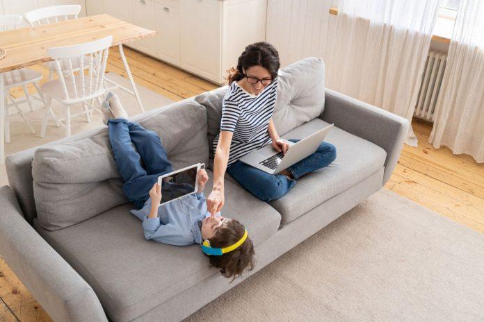 Com o home office, o relacionamento com os filhos melhorou?; mãe usa computador sentada no sofá e mexe no rosto de menino deitado com pernas para cima no sofá e tablet nas mãos