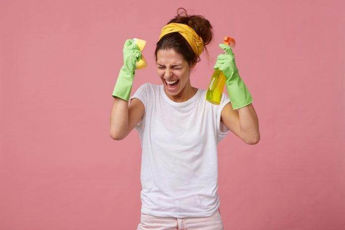 Exaustos, pais acabam sofrendo de 'burnout parental' na pandemia; mulher de faixa amarela no cabelo, com expressão de enlouquecida, tem as mãos para o alto, usa luvas e segura produto de limpeza