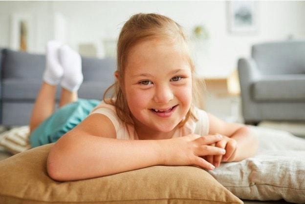 Campanha pede prioridade na vacinação das pessoas com síndrome de Down; menina com síndrome de Down olha sorridente para a câmera