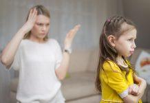 Falar mal do (da) parceiro (a) para o filho pode impactar na sua formação psicológica; mãe com a mão aberta e outra na cabeça está ao fundo e olha para a filha que está de costas para ela e com expressão de chateada