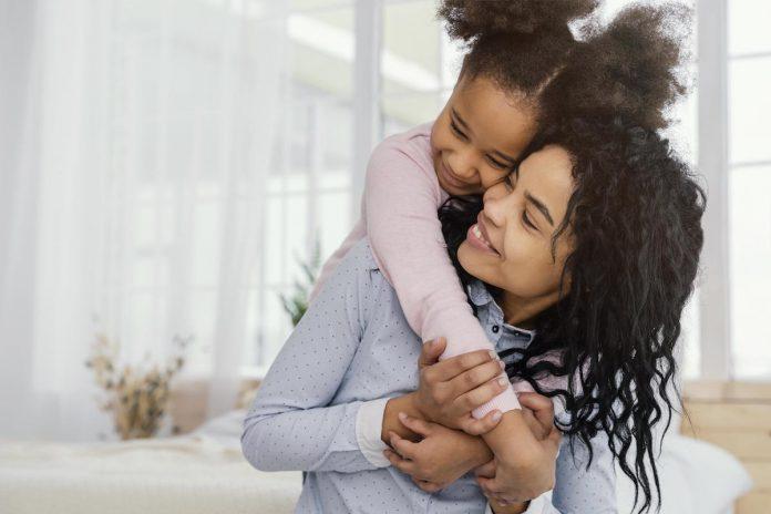Existe uma grande diferença entre ter filhos e ser mãe; mãe de cabelos crespos segura filha na corcunda e ambas se olham sorridentes