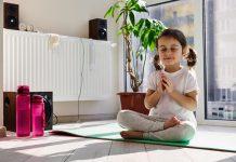 Crianças na pandemia: menos tela, mais meditação; menina de cabelos presos nos dois lados está sentada sob tapetinho com pernas cruzadas, olhos fechados e mãos palma sob palma