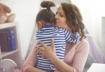 A pandemia deixou os pais exaustos ; mãe de olhos fechados abraça filha